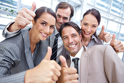 Buy stock photo Cropped view of a group of businesspeople putting their hands in together and giving the thumb's up gesture