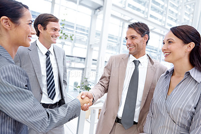 Buy stock photo Group of businesspeople shaking hands and smiling during a meeting