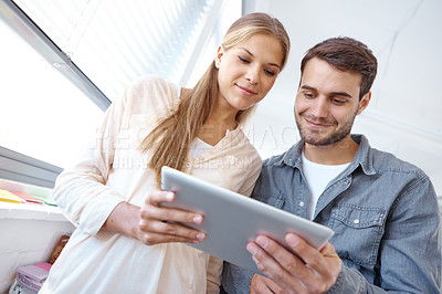 Buy stock photo Low angle shot of two young office workers holding a digital tablet together