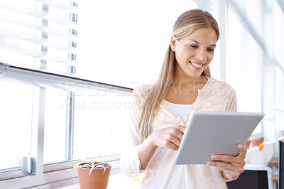 Buy stock photo Low angle shot of a young female designer holding a digital tablet