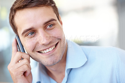 Buy stock photo Closeup portrait of a handsome young business professional talking on his mobile phone