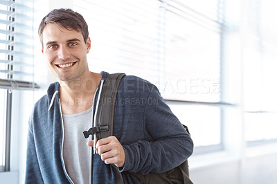 Buy stock photo Portrait of a young male university student carrying a backpack and standing in a hallway