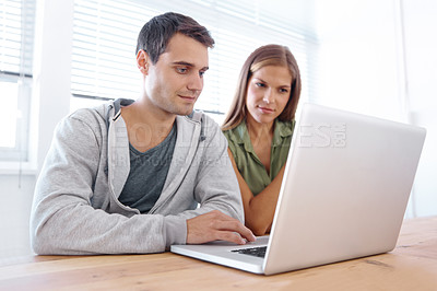 Buy stock photo Shot of two young university students working on a laptop together