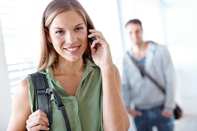 Buy stock photo Portrait of a female university student talking on a cellphone with a male student standing in the background