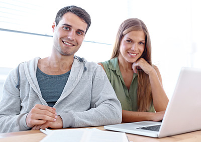 Buy stock photo Portrait of two university students sitting at a table working on a laptop together