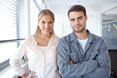 Buy stock photo Two casual business colleagues smiling at the camera with their arms folded