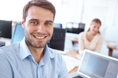Buy stock photo Handsome young businessman sitting at his desk with his co-worker in the background - copyspace