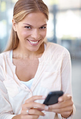 Buy stock photo Lovely young businesswoman smiling at the camera while sending a text - copyspace