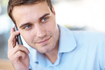 Buy stock photo Handsome young businessman looking sideways while chatting on his cellphone - copyspace