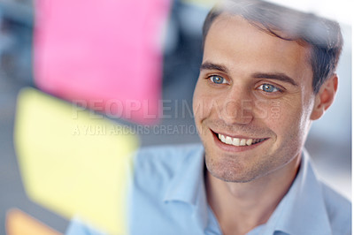 Buy stock photo Smiling young businessman looking at post-it notes stuck to a glass wall - copyspace