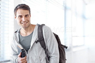 Buy stock photo Handsome young student standing with a backpack slung over his shouder and holding a book- copyspace