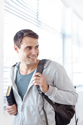 Buy stock photo Handsome young student with a backpack slung over his shouder and holding a book- copyspace