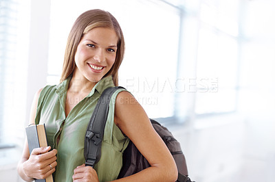 Buy stock photo Lovely young student holding a book with a backpack slung over her shoulder - portrait