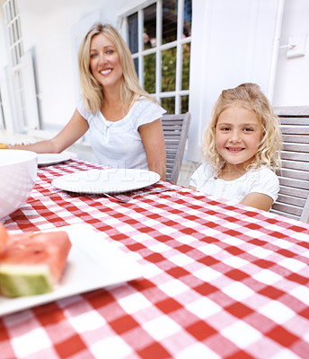 Buy stock photo A cute young girl sitting with her mother at the lunch table