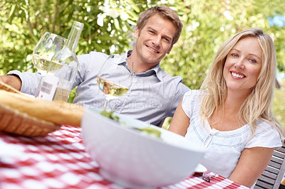 Buy stock photo A mature couple enjoying a glass of wine with their lunch on a bright summer's day