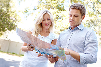 Buy stock photo A mature couple looking at a map while out on a walk