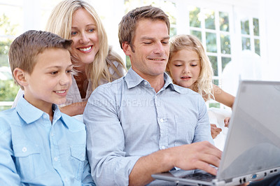 Buy stock photo A happy family browsing the internet together on a laptop