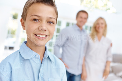 Buy stock photo Portrait of a young boy smiling with his family blurred in the background