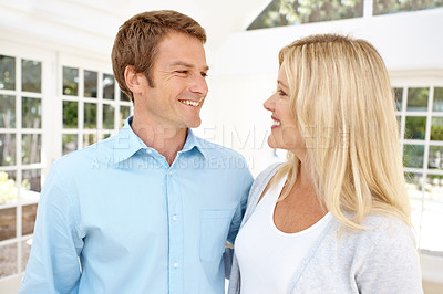 Buy stock photo A happy mature couple looking at one another while standing in their lounge