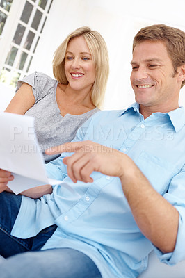 Buy stock photo A mature couple going over a document together while sitting in the lounge