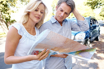 Buy stock photo A lost couple standing outside their car looking at a map