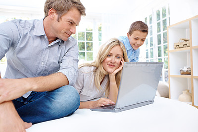 Buy stock photo A mother, father and their son browsing on their laptop