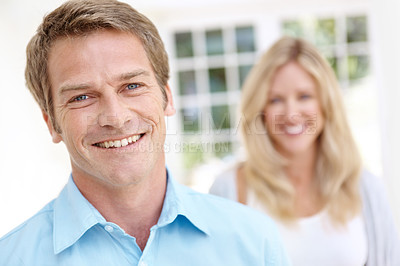 Buy stock photo Portrait of a handsome man with his wife standing in the background