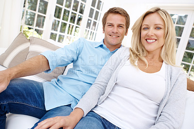 Buy stock photo Portrait of a smiling couple sitting on the couch
