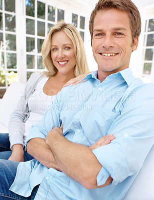 Buy stock photo Portrait of a smiling couple with the man folding his arms