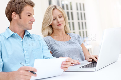 Buy stock photo A man and woman looking on a laptop while the man looks over a document