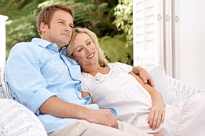 Buy stock photo A happy couple sitting on a chair outside looking at bliss