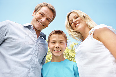Buy stock photo Young boy standing between his parents and looking down