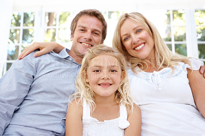 Buy stock photo Cute little girl sitting between her parents at home