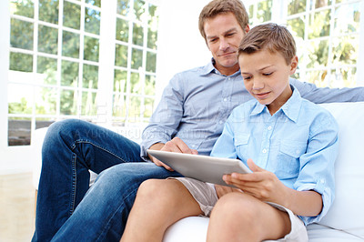 Buy stock photo Cute young boy using a digital tablet with his father