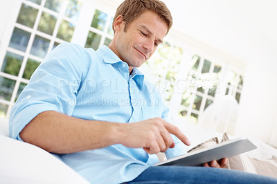 Buy stock photo Handsome mature man using a digital tablet while a home