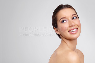 Buy stock photo Smiling young woman with perfect skin against a gray background