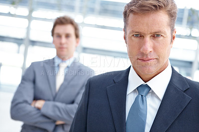 Buy stock photo An dedicated executive standing with a colleague blurred in the background