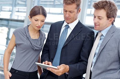 Buy stock photo A business team going over the brief on a digital tablet