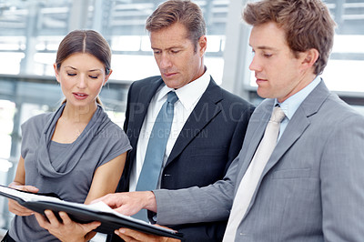 Buy stock photo A business team going over their notes before an important meeting