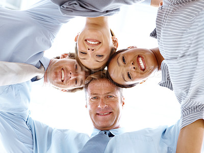 Buy stock photo Low view of a business team putting their heads together and smiling