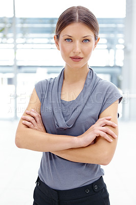 Buy stock photo Portrait of a pretty young businesswoman crossing her arms and smiling