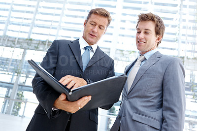 Buy stock photo Two handsome businessmen looking at a file