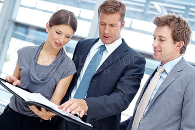 Buy stock photo Three attractive businesspeople looking together at a file