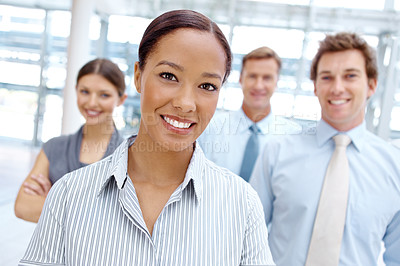 Buy stock photo A beautiful young businesswoman smiling at the camera with her team in the background