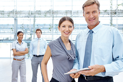 Buy stock photo A handsome young businessman and -woman smiling at the camera with their team in the background