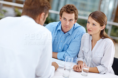 Buy stock photo A young couple listening to the advice of a financial advisor