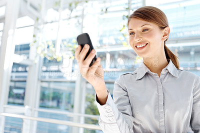 Buy stock photo A beautiful young businesswoman reading a text message on her cellphone