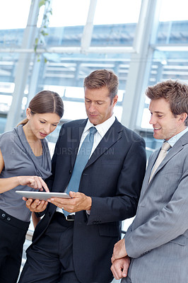 Buy stock photo Group of three businesspeople looking at a digital tablet together