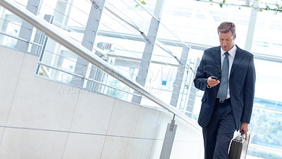 Buy stock photo Mature businessman texting on his mobile while walking alongside copyspace