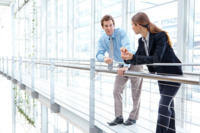 Buy stock photo Two young businesspeople having a discussion alongside a railing